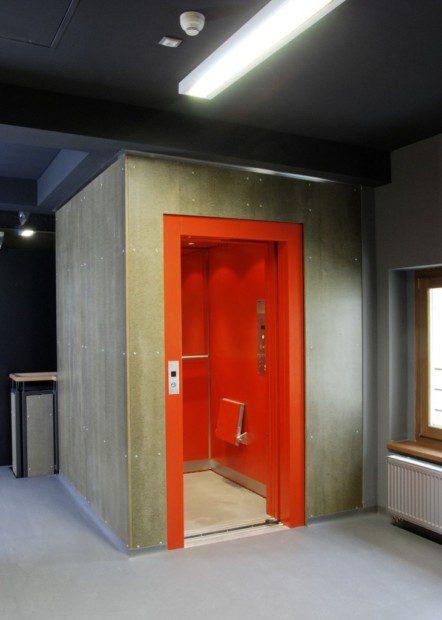 Ocelová konstrukce hydraulického výtahu v exteriéru na fasádě objektu